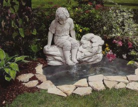 Laguna Bahamas is a boy sitting on rocks by a pond cement stone water feature